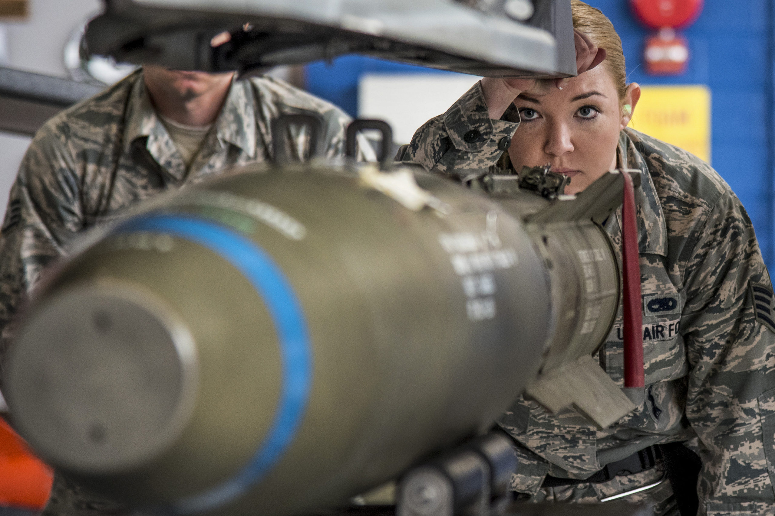 Military lady inspecting bomb